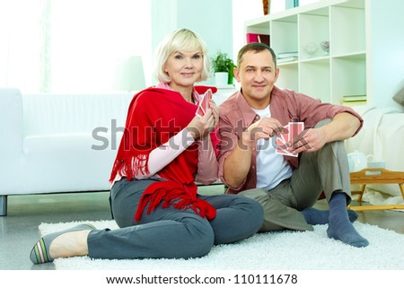 Portrait of mature man and his wife playing cards at home - stock photo