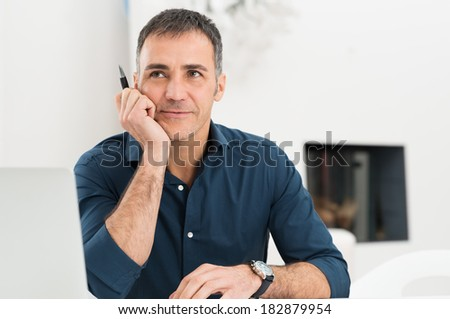 Portrait Of Mature Man Daydreaming While Holding Pen - stock photo