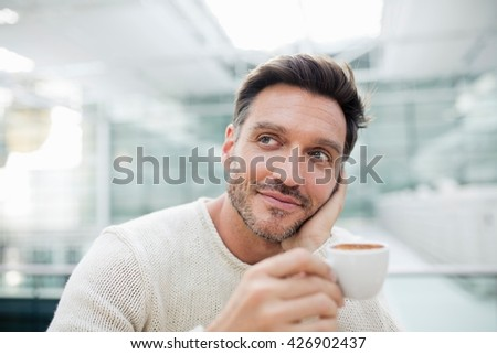 Portrait of mature man drinking espresso in city cafe