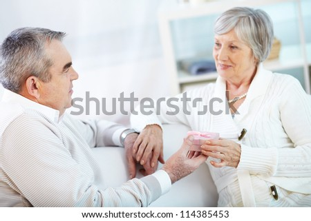 Portrait of mature man giving small giftbox to his wife