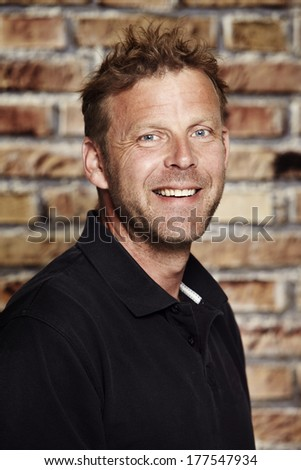 Portrait of mature man in front of brick wall