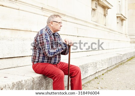Portrait of mature man in glasses and plaid shirt resting leaning on his wooden walking stick - stock photo
