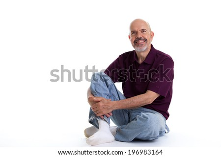 Portrait of mature man in purple polo shirt sitting isolated on white - stock photo