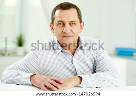 Portrait of mature man looking at camera while sitting on sofa - stock photo