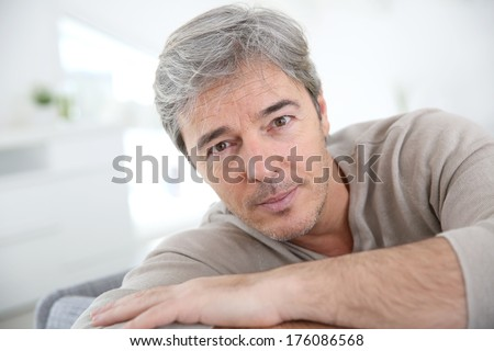Portrait of mature man relaxing at home in sofa