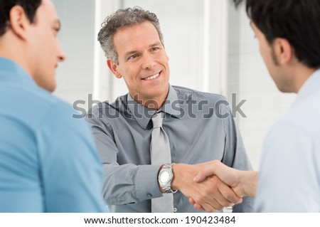 Portrait Of Mature Man Shaking Hand With Young Businessman - stock photo