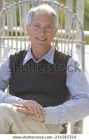 Portrait of mature man sitting in chair