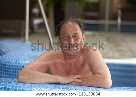 Portrait of mature man smiling in swimming pool.
