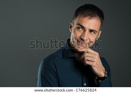 Portrait Of Mature Man Thinking A Strategy With Hand On Chin On Grey Background - stock photo