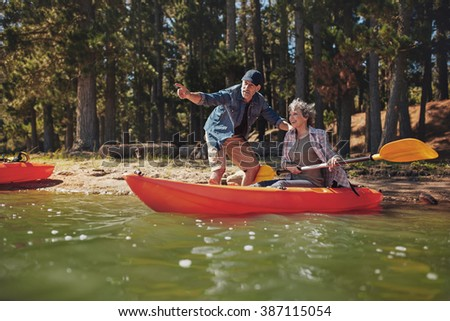 Portrait of mature man with a woman in a kayak in the lake. man showing something interesting to woman holding paddles. Senior couple enjoying a day at the lake. - stock photo