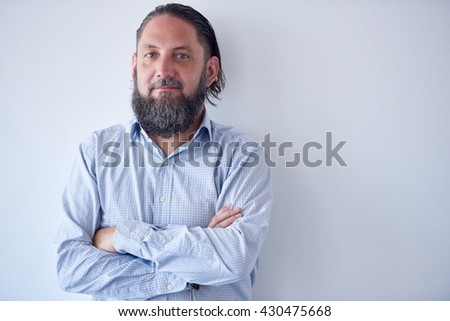 Portrait of Mature man with arms crossed agianst white wall