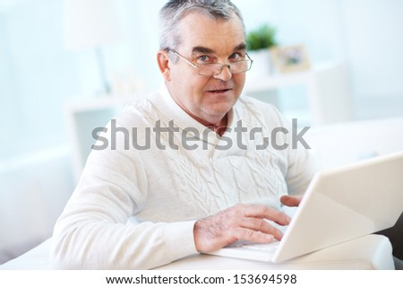 Portrait of mature man working with laptop and looking at camera - stock photo