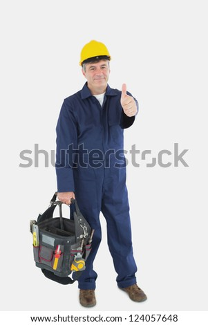 Portrait of mature mechanic with tool bag showing thumbs up sign over white background - stock photo