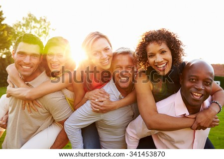 Portrait Of Mature Men Giving Women Piggy Backs - stock photo