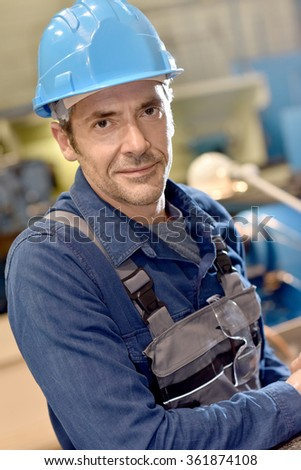Portrait of mature metal worker standing in workshop