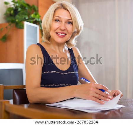 Portrait of mature positive woman with financial documents in office interior