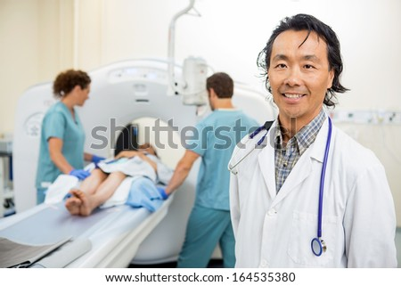 Portrait of mature radiologist with nurses preparing patient for CT scan in hospital - stock photo