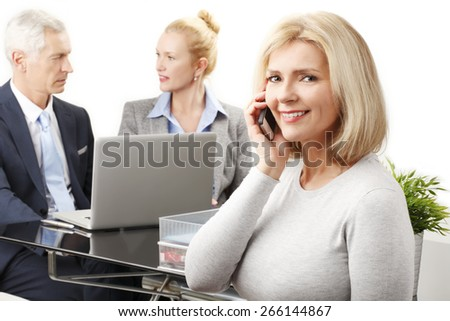 Portrait of mature sales woman making call while sales team working at background with laptop. Isolated on white background.