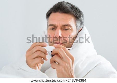 Portrait Of Mature Sick Man Wrap In Blanket Looking At Thermometer - stock photo