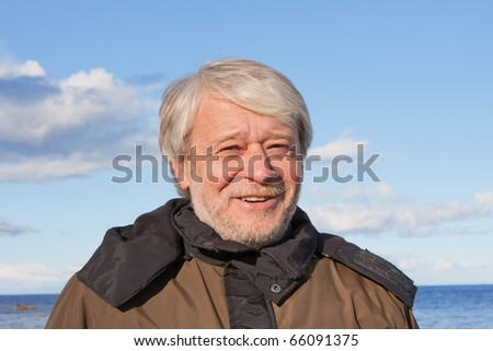 Portrait of mature smiling man with grey hair at the Baltic sea in autumn day. - stock photo