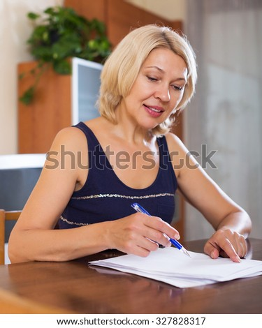 Portrait of mature smiling woman with financial documents in office interior