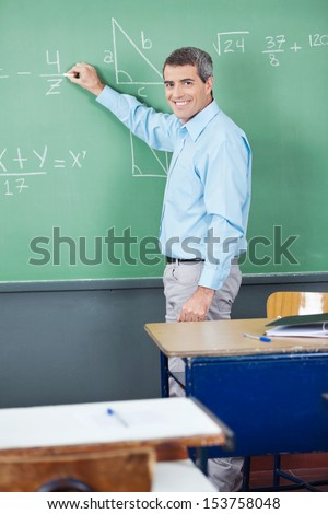 Portrait of mature teacher writing on board in classroom - stock photo