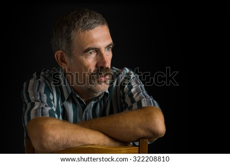 Portrait of mature Ukrainian peasant in low key - stock photo