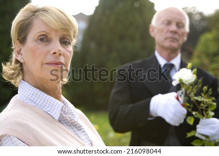 Portrait of mature woman, butler pruning bush in background