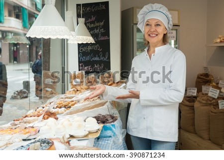 Portrait of mature woman chef at confectionery display with pastry - stock photo