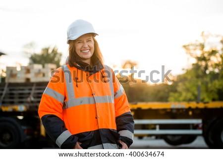 Portrait of mature woman engineer wearing protective orange jacket in work - stock photo