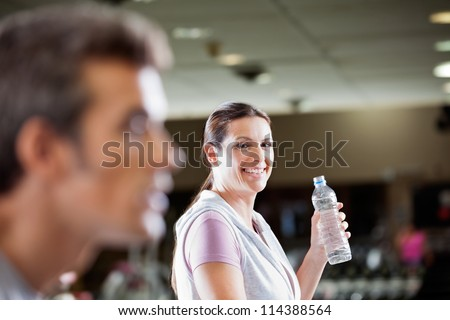 Portrait of mature woman holding bottle of water at health club - stock photo
