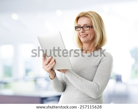 Portrait of mature woman holding digital tablet while standing at office.  - stock photo