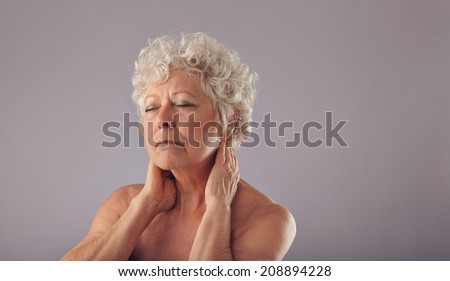 Portrait of mature woman holding her neck in discomfort against grey background. Shirtless senior woman with neck pain. - stock photo