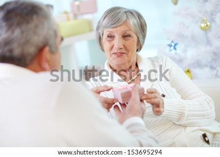 Portrait of mature woman holding small giftbox given by her husband - stock photo