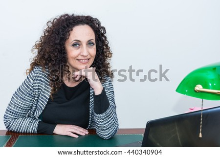 Portrait of mature woman in her studio. With curly hair, blacks or dark, green eyes, on white or clear. - stock photo