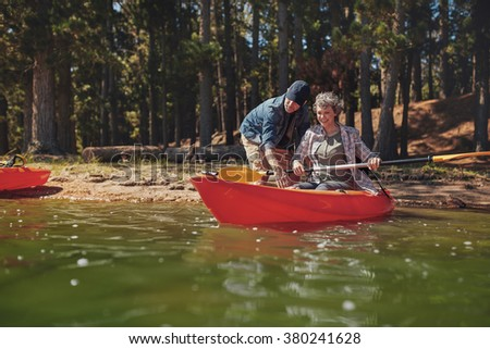 Portrait of mature woman learning to row in kayak. Man teaching kayaking to woman at the lake. - stock photo