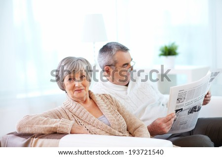 Portrait of mature woman looking at camera on background of her husband reading newspaper - stock photo