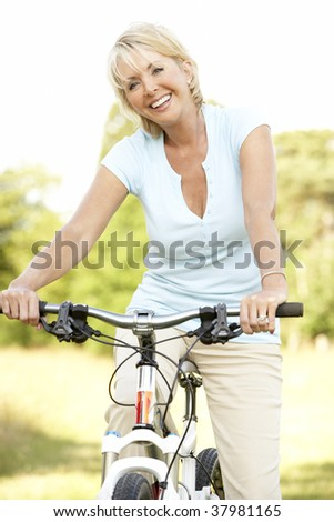 Portrait of mature woman riding cycle in countryside - stock photo