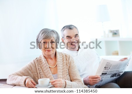 Portrait of mature woman with cup looking at camera on background of her husband reading newspaper - stock photo