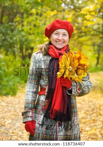 Portrait of mature woman with maple leaves in autumn park