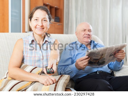 Portrait of  mature woman with TV remote against elderly man with newspaper in home interior - stock photo