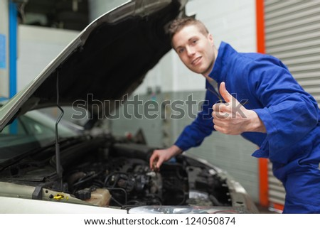 Portrait of mechanic gesturing thumbs up as he checks oil level of car - stock photo