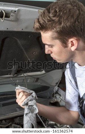 Portrait of mechanic repairing under car hood