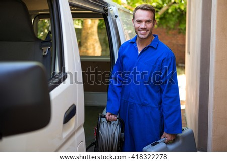 Portrait of mechanic with a tool box and cable standing near a car - stock photo