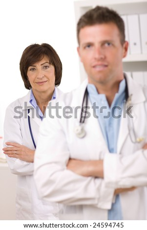 Portrait of medical doctors male and female at office. Focus on woman.