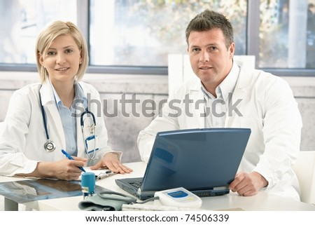 Portrait of medical doctors working together in office.? - stock photo