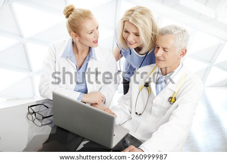 Portrait of medical team sitting at desk in front of computer and consulting. Medical group.