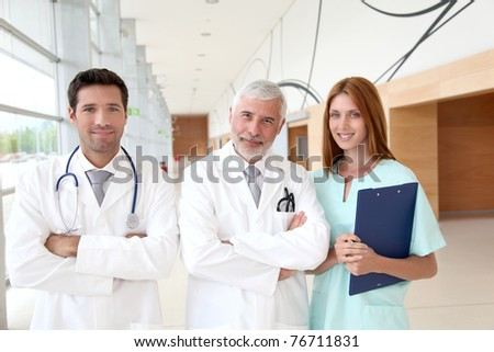 Portrait of medical team standing in hospital hall - stock photo