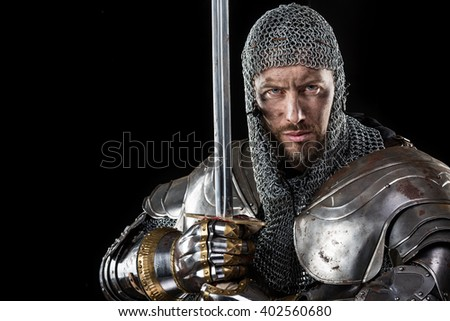 Portrait of Medieval Dirty Face Warrior with chain mail armour and red cross on sword. Black Background - stock photo