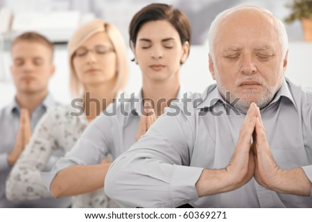 Portrait of meditating businessteam, with senior businessman in focus, exercising with closed eyes.? - stock photo